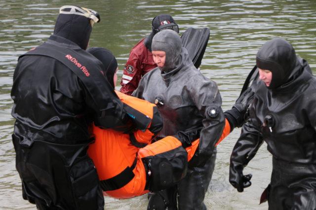 Matalassa päässä sukeltaja nostetaan kevyesti kahden kaverin avustuksella. Yläpäässä oleva tarttuu pelastettavan ranteista kiinni kunnon otteella.