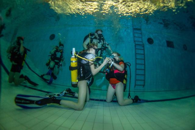 Junior scupa-kurssilaiset harjoittelevat ahkerasti kaikenlaisia vedenalaisia taitoja. Kurssin yksi kouluttajista , Teemu, katselee kuinka harjoitus sujuu.